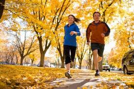 photo of couple running in fall