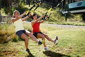 photo of pair of women doing band workout outdoors